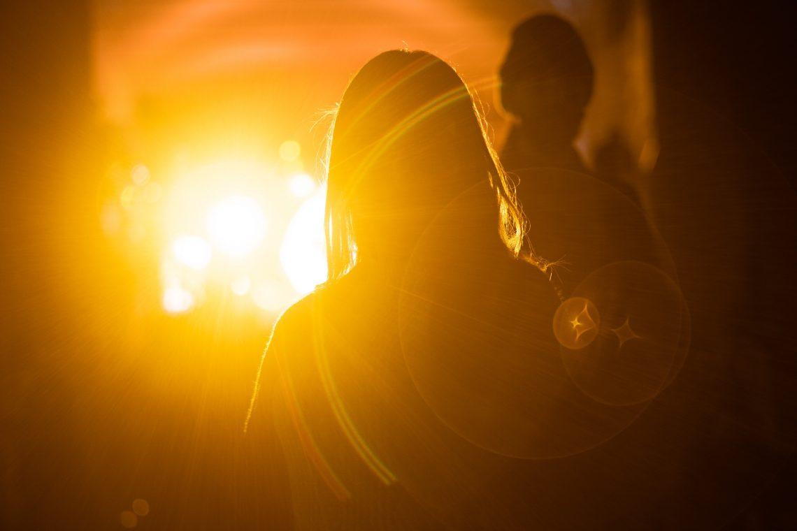 Two people walk towards a glowing yellow sun.